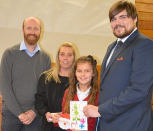 Winner Jessica Judd with her winning Christmas Card Competition entry picture alongside Headteacher Ed Seeley, senior midday supervisor Jane Bowler and PK Education consultant Thomas Martin